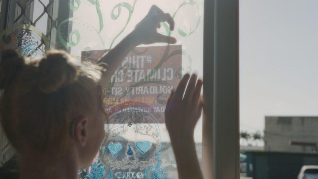 """SÜDWESTRUNDFUNK SCHAU IN MEINE WELT!, """"Sabyah kämpft! Gegen Kohleabbau"""", am Sonntag (20.06.21) um 20:30 Uhr. Sabyah befestigt einen Flyer an der Tür eines Jugendzentrums in ihrer Gegend, um für den Protest gegen den Bau einer weiteren Kohlemine in Queensland, Australien, zu werben. © SWR/Irja von Bernstorff, honorarfrei - Verwendung gemäß der AGB im engen inhaltlichen, redaktionellen Zusammenhang mit genannter SWR-Sendung bei Nennung """"Bild: SWR/Irja von Bernstorff"""" (S2). SWR Presse/Bildkommunikation, Baden-Baden, Tel: 07221/929-22202, foto@swr.de"""